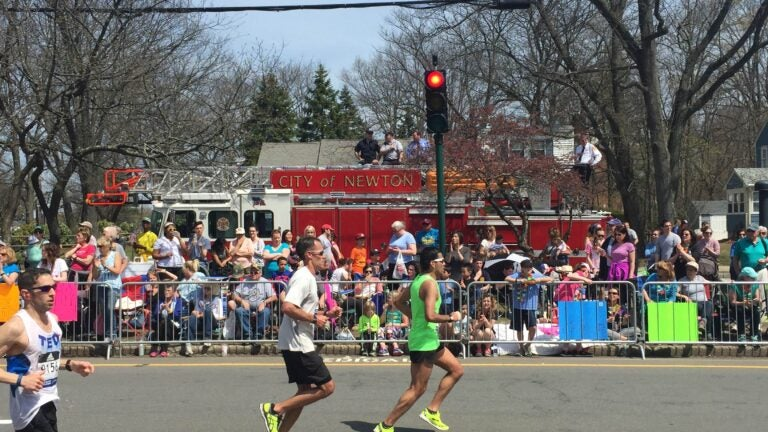Firefighters cheer runners from a ladder truck near mile 18 in Newton.