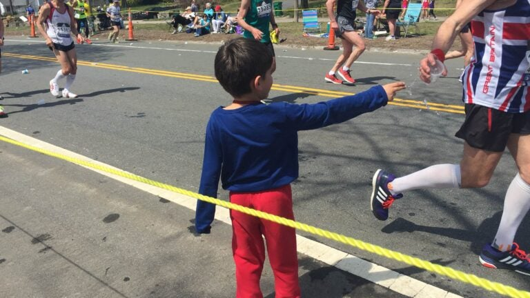 Family and friends of Mike Denaro handed out water to Boston marathon runners in Newton.