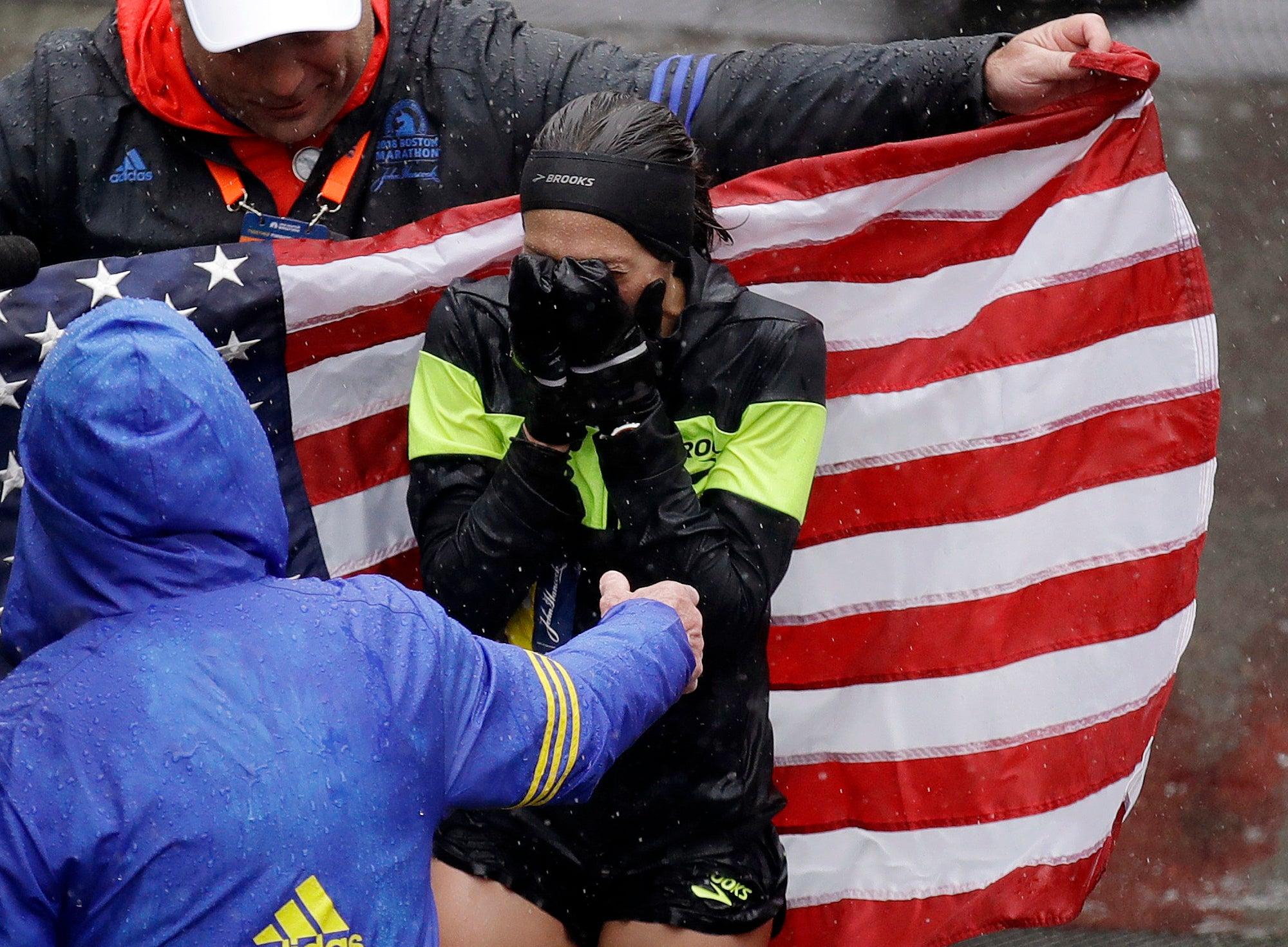 Desiree Linden, of Washington, Mich., celebrates after winning the women's division of the 122nd Boston Marathon.