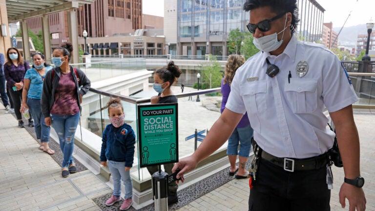 "A security guard adjusts a ""Social Distance"" sign"