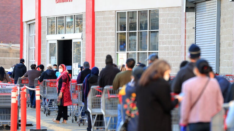 Customers waiting to enter a Costco store.