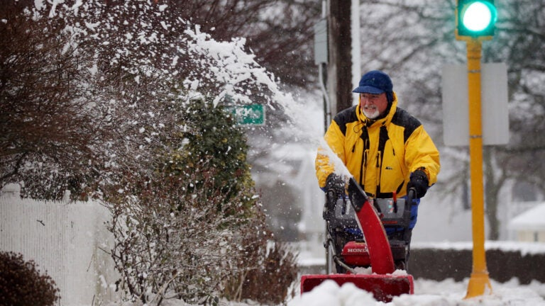 A man uses a snowblower to clear the sidewalk.