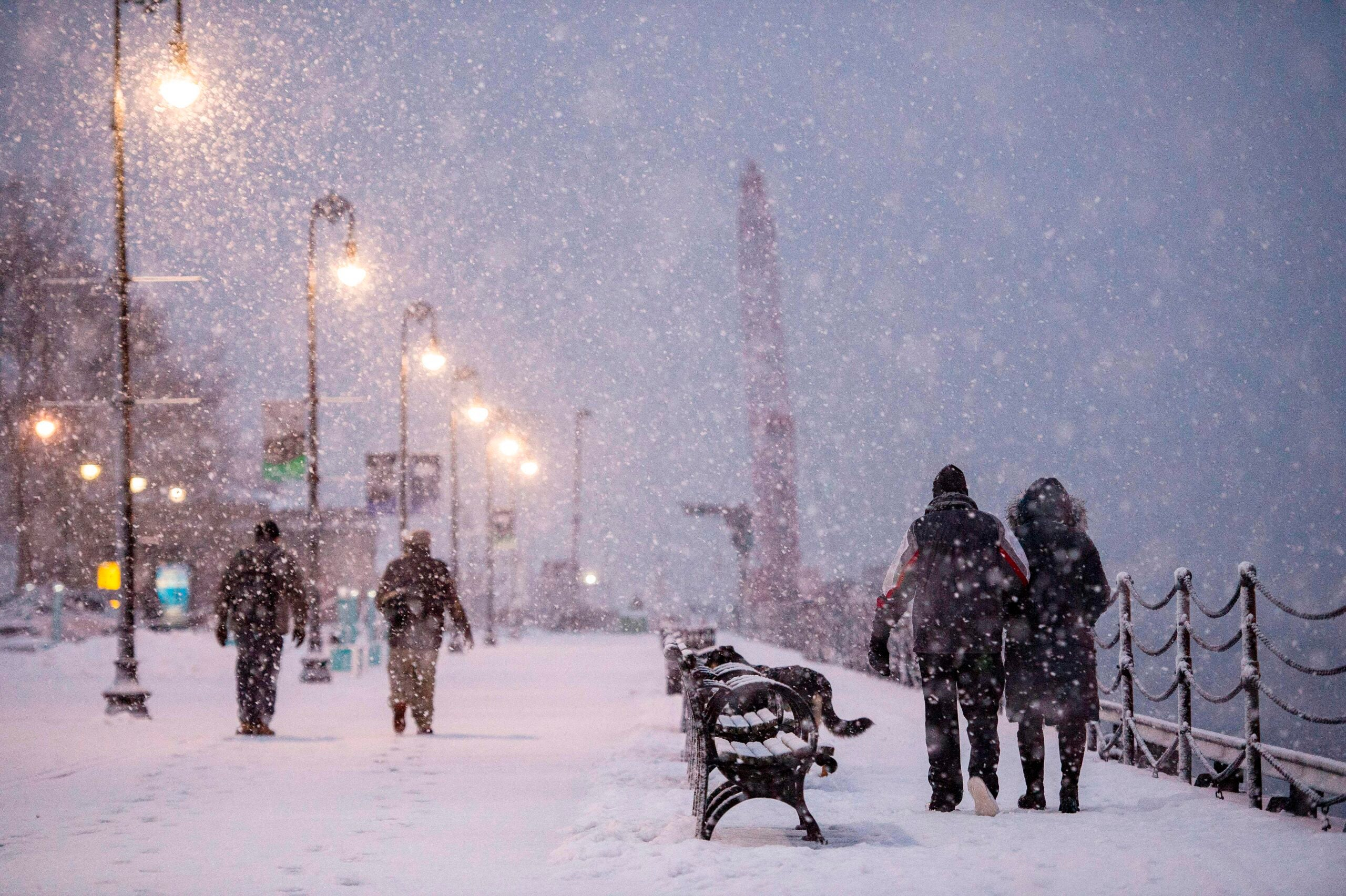 People walk through heavy snow fall in the Navy Yard during a winter storm.