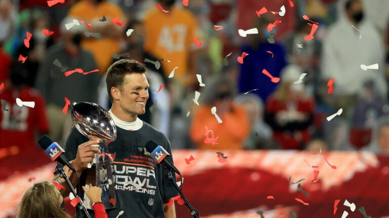 Tom Brady hoists the Vince Lombardi Trophy.