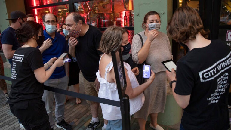 A customer shows her vaccination card to a host at City Winery, a restaurant in New York, on May 26, 2021